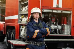 Fireman firefighter in action standing near a firetruck. Emer. Gency safety . Protection, rescue from danger royalty free stock photography