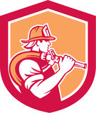 Fireman Firefighter Holding Fire Hose Shoulder Shield. Illustration of a fireman fire fighter emergency worker holding fire hose over his shoulder viewed from Royalty Free Stock Photos