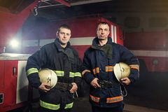 Fireman firefighters in action standing near a firetruck. Eme royalty free stock photo
