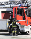 Fireman and a firetruck in the barracks of the fire brigade Stock Photos