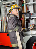 Fireman Fixing Water Hose In Truck At Fire Station Royalty Free Stock Photos