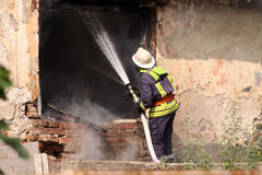 Fireman. The fireman in the form with hose extinguish a fire Stock Photo