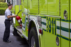 Fireman getting ready. Fireman taking out equipment from his fire truck Stock Image
