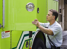 Fireman getting ready. Fireman taking out equipment from his fire truck Stock Photo
