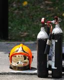 Fireman helmet and fire extinguishers. A modern day fireman's helmet and two fire extinguishers Royalty Free Stock Images