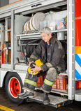 Fireman Holding Coffee Cup While Sitting In Truck Royalty Free Stock Images