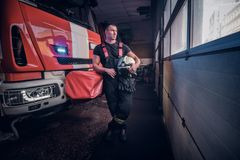 Young fireman holding a jacket and protective helmet in a garage of a fire department, leaning on a fire engine and. Fireman holding a jacket and protective royalty free stock photo