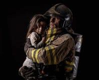 Fireman holding little girl on black. Dirty firefighter in uniform holding little saved girl standing on black background Royalty Free Stock Images