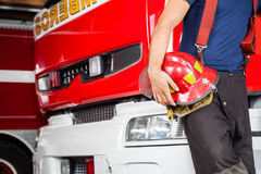 Fireman Holding Red Helmet While Leaning On Truck Royalty Free Stock Image