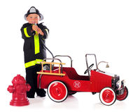 Fireman Hosing. A preschool boy by a fire truck and hydrant and wearing fireman gear, points his hose at the viewer.  Isolated on white Stock Image
