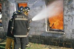 Fireman hosing down a burning building Royalty Free Stock Photo