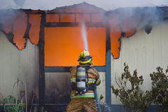 Fireman at a House Fire. One firefighter on hose defending at a structure fire stock photos