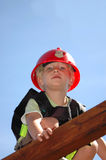 Fireman kid. A beautiful little blond and blue eyed boy child head portrait with cute expression in the handsome face dressed up with a red helmet playing stock photography