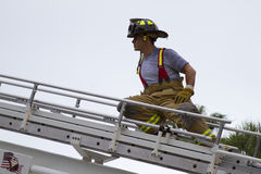 Fireman on ladder. Fireman climbing a ladder with bunker gear on royalty free stock image