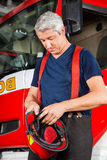 Fireman Looking At Helmet Against Firetruck Royalty Free Stock Images