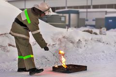 Fireman makes a fire outdoors. Training the pressure of the open fire in the winter royalty free stock image