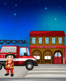 A fireman near the fire station. Illustration of a fireman near the fire station Stock Image