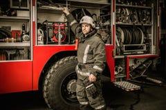 Fireman near firefighting truck. Fireman taking equipment from firefighting truck Stock Photos