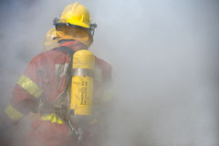 Fireman in operation surround with smoke. Fireman in fire fighting suit working surround with smoke Stock Image