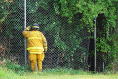 Fireman Peering Through Fence Royalty Free Stock Image