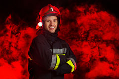Fireman posing against red smoke. Royalty Free Stock Photo