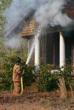 Fireman putting fire out Stock Photos
