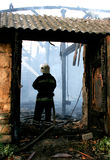 Fireman Putting out a House Fire. Fireman spraying water in a smouldering burnt out house Stock Images