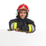 Fireman in red helmet lean on the blank banner Stock Photo