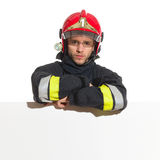 Fireman in red helmet lean on the blank banner Royalty Free Stock Photo