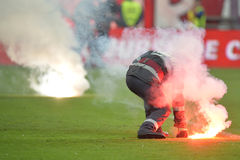 Fireman remove flares from the football pitch Royalty Free Stock Photography