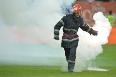 Fireman remove flares from the football pitch Royalty Free Stock Photo