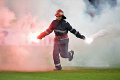Fireman remove flares from the football pitch. During the Romanian football derby between Dinamo Bucharest and Steaua Bucharest Royalty Free Stock Image