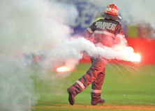 Fireman remove flares from the football pitch Royalty Free Stock Image