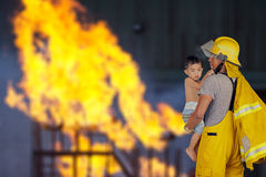 Fireman rescued the child from the fire. Firefighter, fireman rescued the child from the fire royalty free stock photos