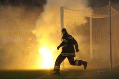 Fireman runs among flairs Royalty Free Stock Photos