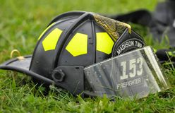 Wet fireman's helmet sitting in the grass. Fireman's helmet sitting on the ground after being used - Black and yellow helmet with water drops on Stock Photo