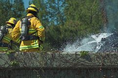 Fireman at scene of car fire. Fireman at the scene of a car fire on side of the freeway Stock Image