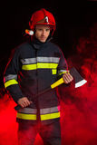 Fireman in smoke holding axe. Royalty Free Stock Photos