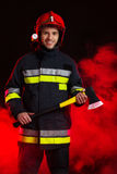 Fireman in smoke posing with axe. Stock Photo