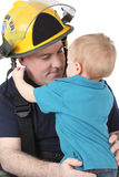 Fireman Son. Toddler son of a fireman looking at him Stock Photos