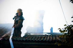 Fireman In a special form on the roof of a burning house Royalty Free Stock Photography