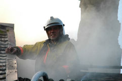 Portrait of fireman in a special form on the roof of a burning house Stock Image