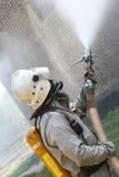 Fireman spraying water Stock Photos