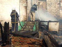 Fireman spraying water firefighters extinguish a fire in an apa. Smoldering remains of a ghetto house with a fireman spraying water firefighters extinguish a Stock Images