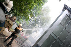 Fireman spraying water firefighters extinguish a fire in an apar Stock Photo
