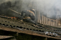 Fireman spraying water. Smoldering remains of a ghetto house with a fireman spraying water firefighters extinguish a fire in an apartment house Royalty Free Stock Photo