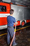 Fireman Spraying Water On Truck During Practice Royalty Free Stock Photography