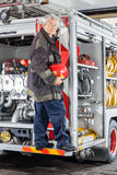 Fireman Standing On Truck At Fire Station Stock Photo
