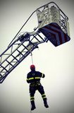 Fireman suspended under the moving platform during an emergency. Courageous fireman suspended under the moving platform during an emergency royalty free stock photo