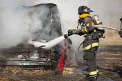 Fireman training on a burning car Royalty Free Stock Images